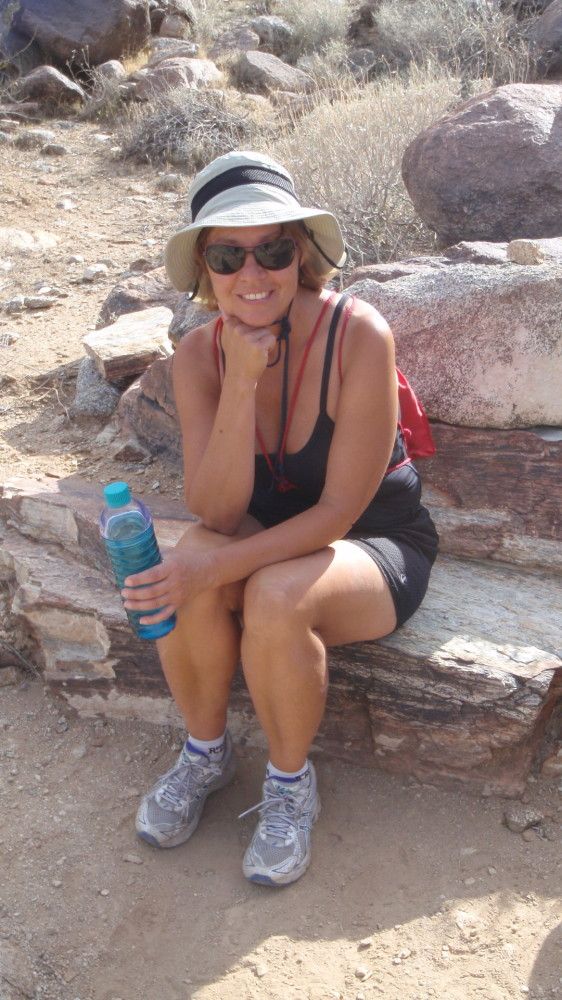 A tired hiker sits on a convenient rock ledge